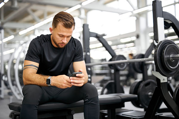 gym manager on his smartphone