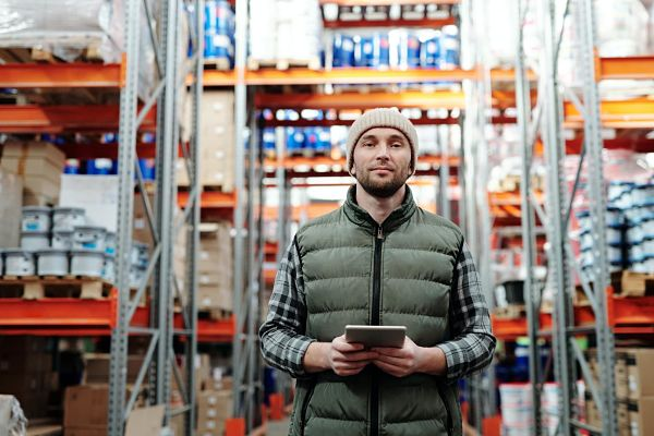 man in a warehouse using a tablet